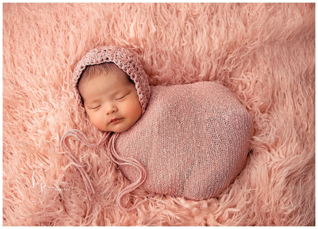 newborn baby girl in pink wrap and bonnet