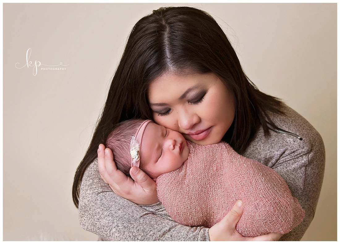 newborn baby girl in pink wrap held by mother