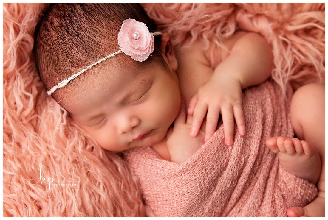 close up of newborn baby girl in pink wrap and pink fur