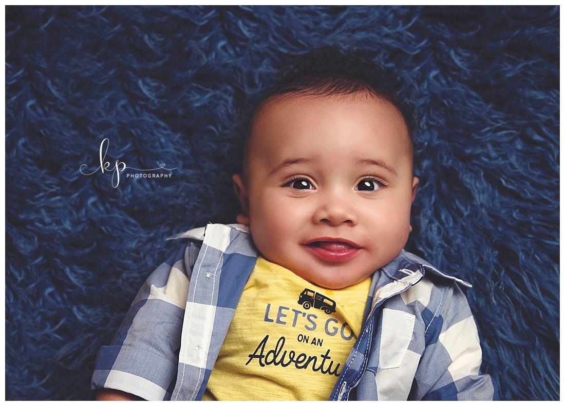 6 month old boy wearing plaid shirt on blue fur rug