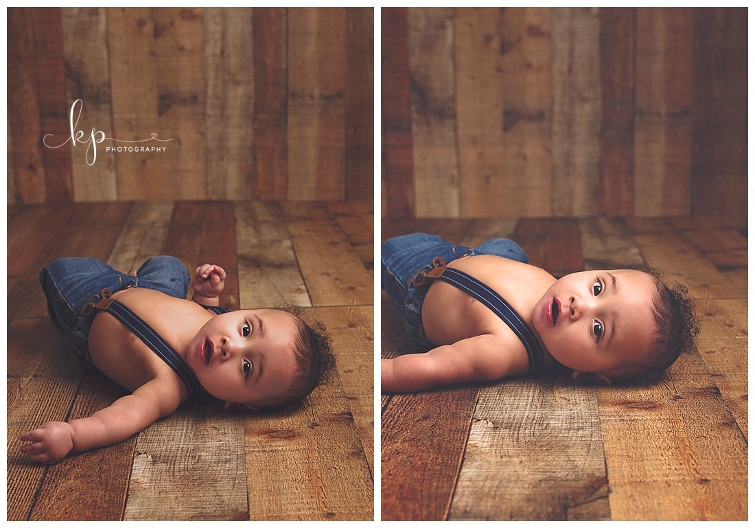 6 month old wearing suspenders laying on wood floor